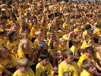 Large group of students wearing yellow t-shirts